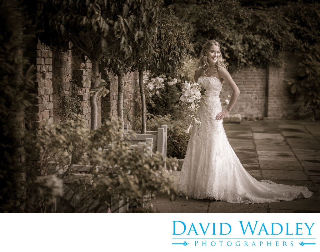 Bride in walled courtyard at Shustoke Barns.