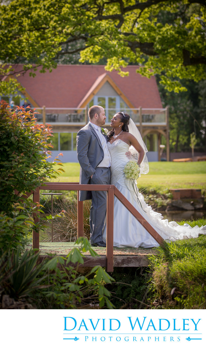 Bride & Groom on bridge with clubhouse at Nailcote Hall.