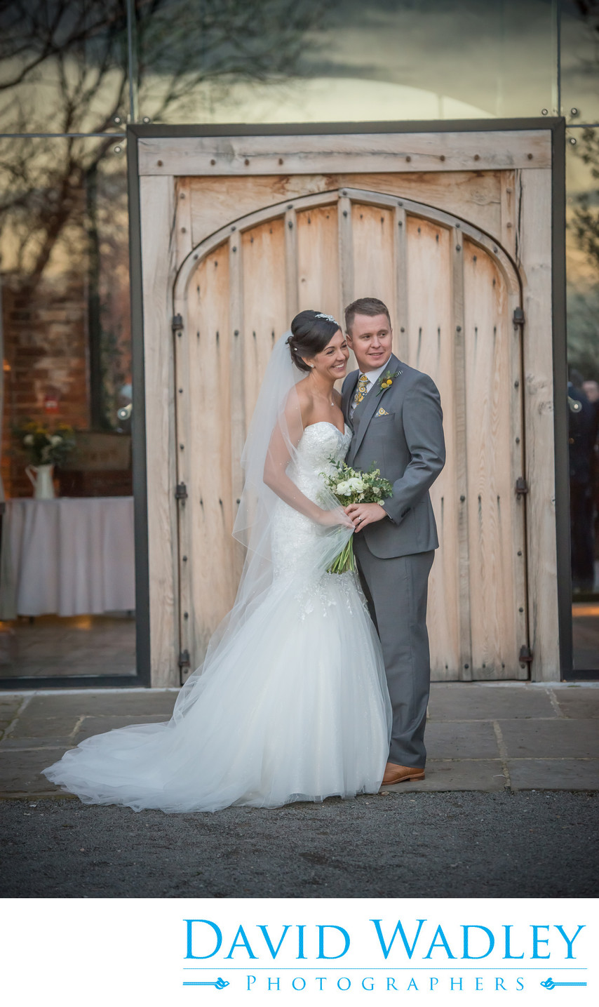 Bride & Groom photographed outside doorway at stunning Shustoke Barn.