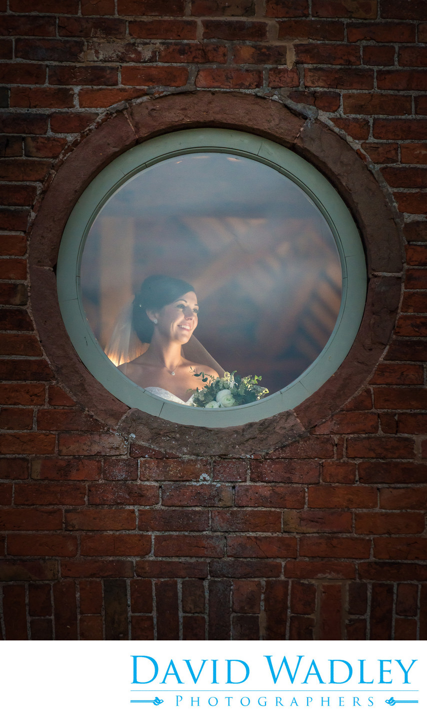 Bride photographed in window at Shustoke Barn.