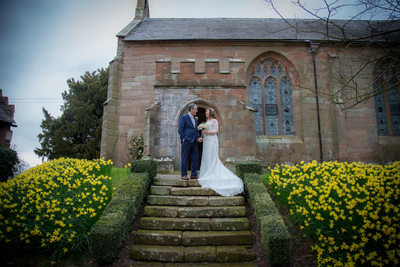 The bride & groom outside the John Morris Hall on their wedding day at Grafton Manor