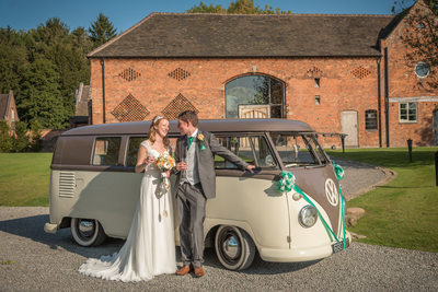 Bride & Groom photographed with VW camper van outside Shustoke Barn.