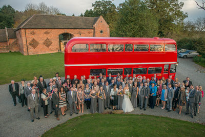 Bride & Groom with all their wedding guests photographed outside stunning Shustoke Barns.