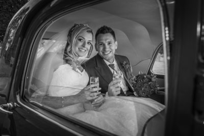 Bride & Groom sitting in wedding car.