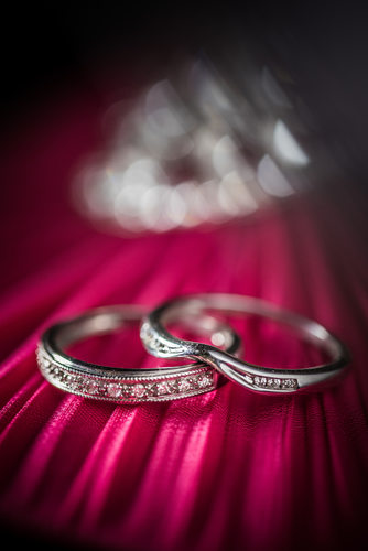 Wedding rings photographed on a red background.