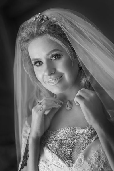 Bride adjusting necklace before wedding in Black & White.