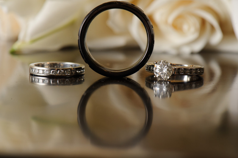 Wedding Ring Reflections with white roses behind.