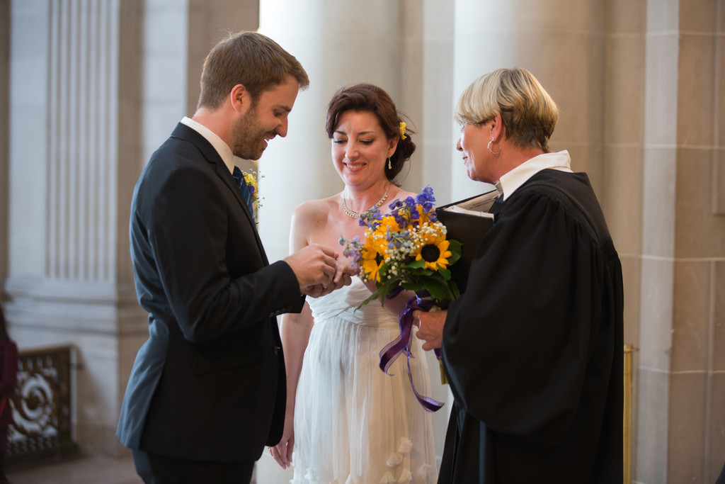 Groom puts ring on bride's hand during Rotunda ceremony
