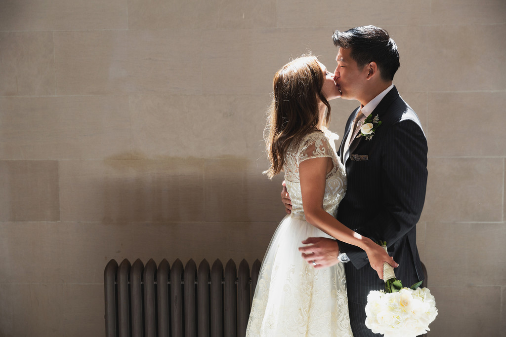 Bride and groom kiss at City Hall
