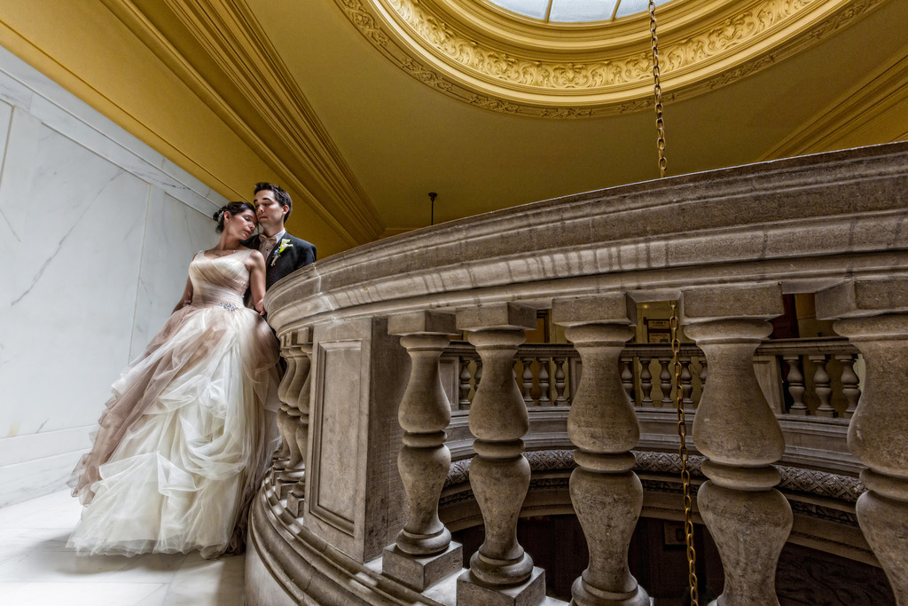 Bride and groom pose on fourth floor landing