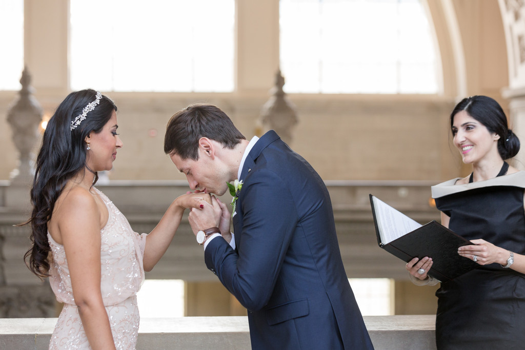 Groom kisses bride's hand during ceremony