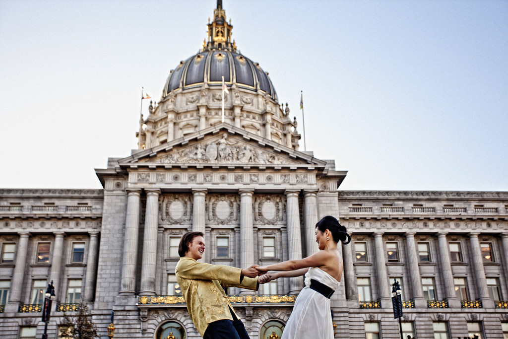 Playful bride and groom outside city hall