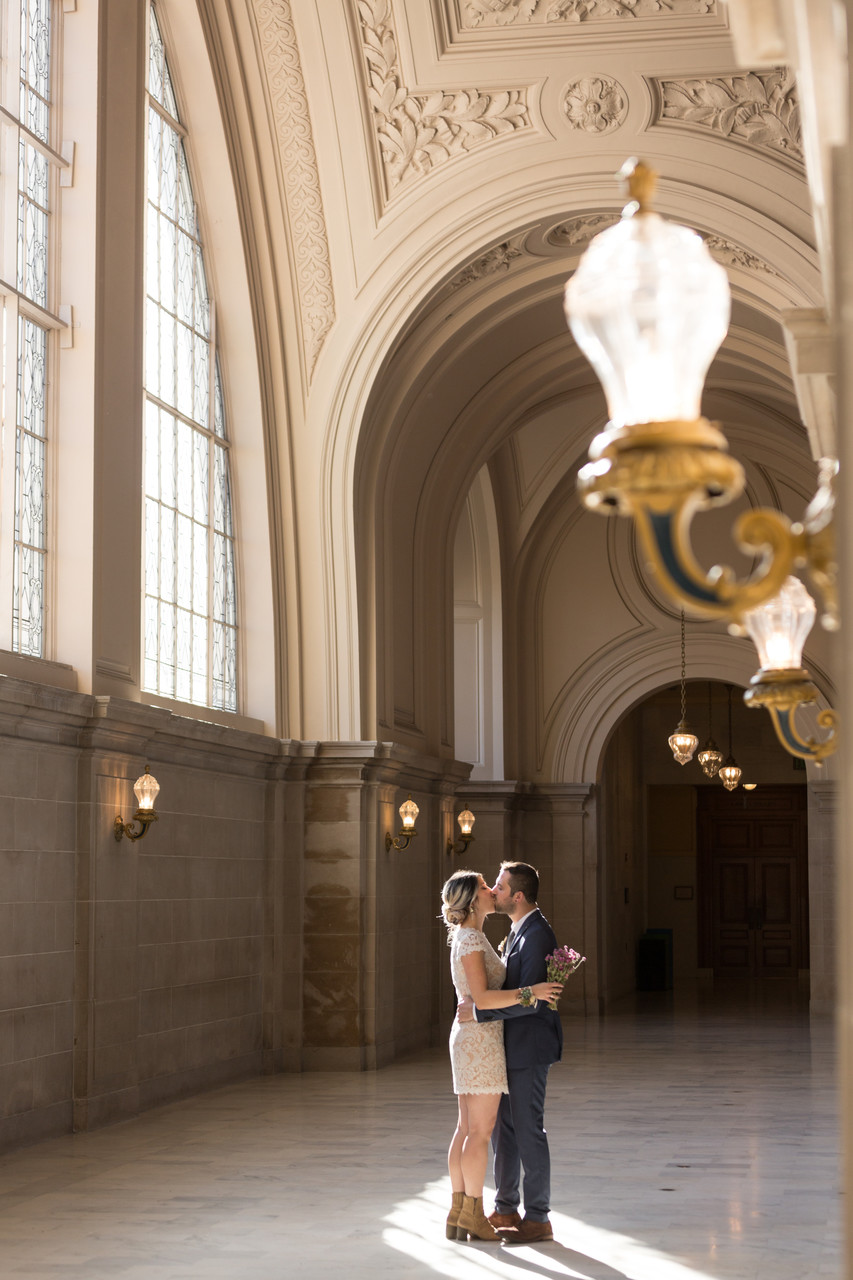 Bride and groom kiss in 4th floor sunlight