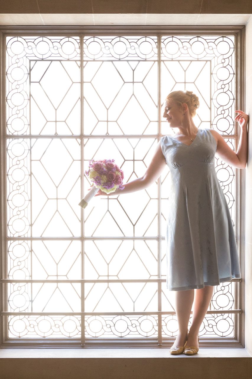 Bride with flowers in big window
