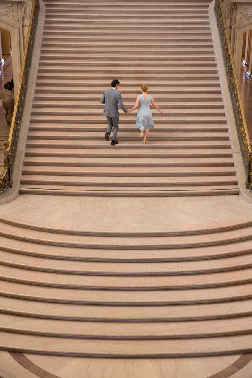 Bride groom ascend San Francisco City Hall staircase