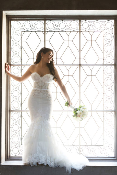 Bride standing in art deco window