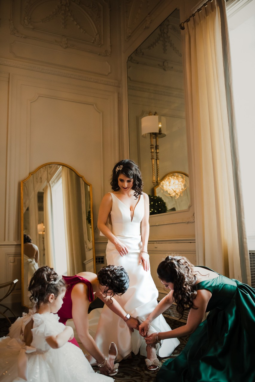 Bride putting on her wedding shoe photos