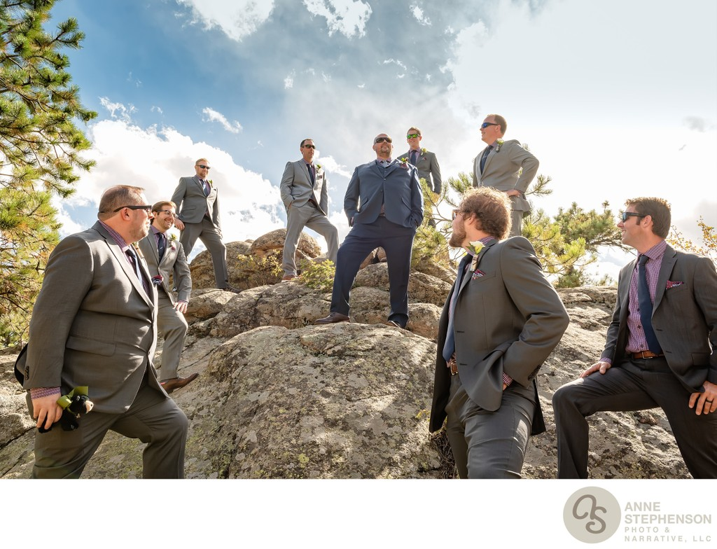 Groom Stands Tall and Proud Atop Rocks with Groomsmen