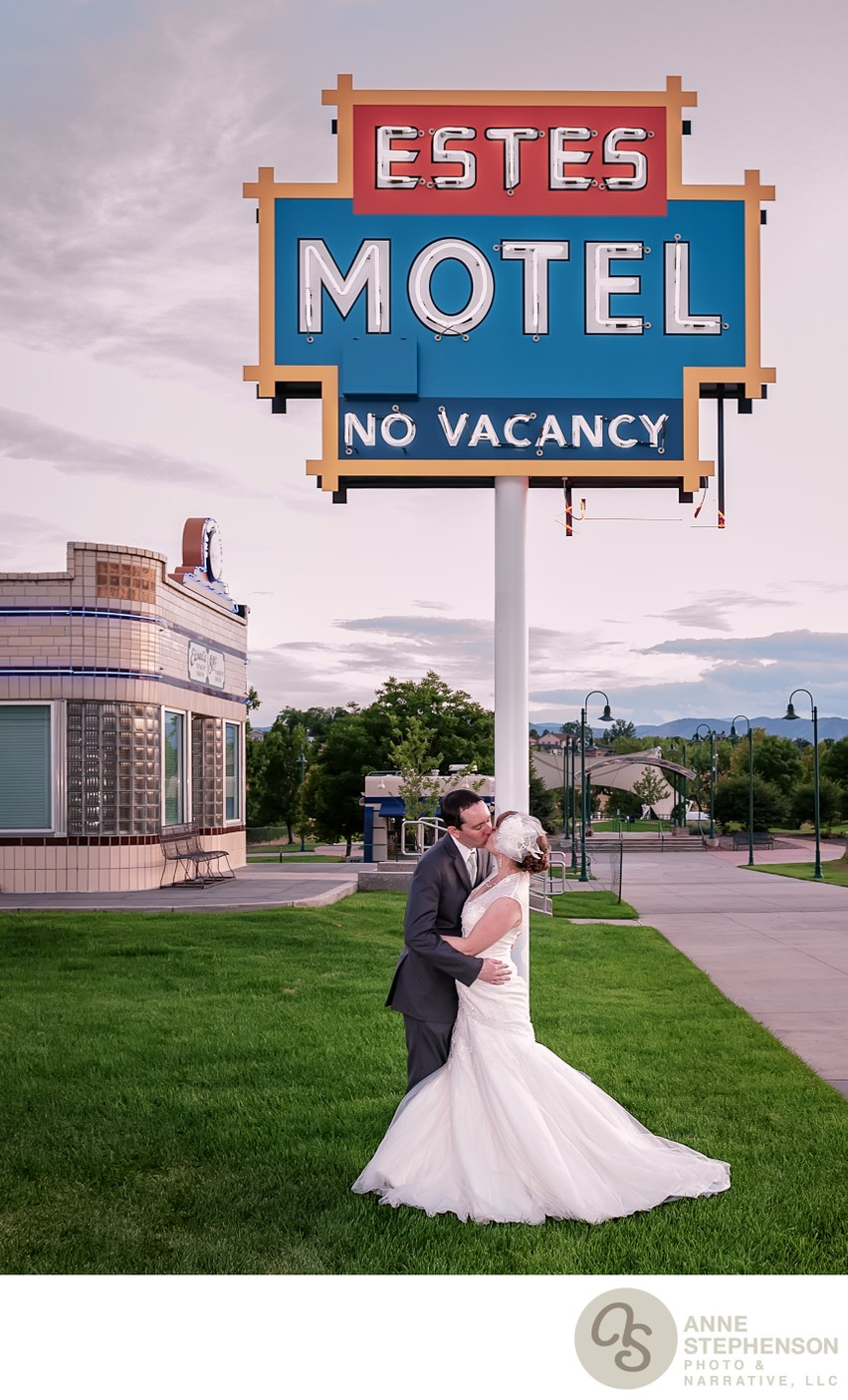 Bride and groom kiss in front of historic motel sign