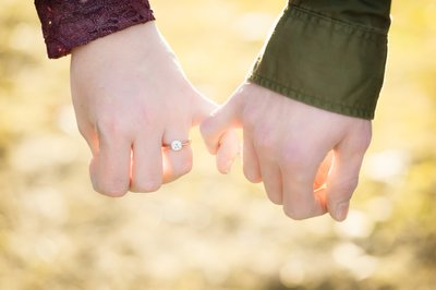 An engaged man and woman hold pinkie fingers showing their love.