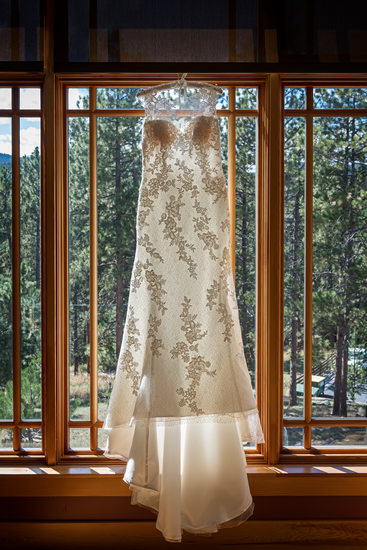 Wedding Dress Framed in Wooden Window with Evergreens