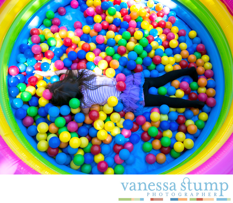 Little girl lying facedown in colorful balls at children's birthday party
