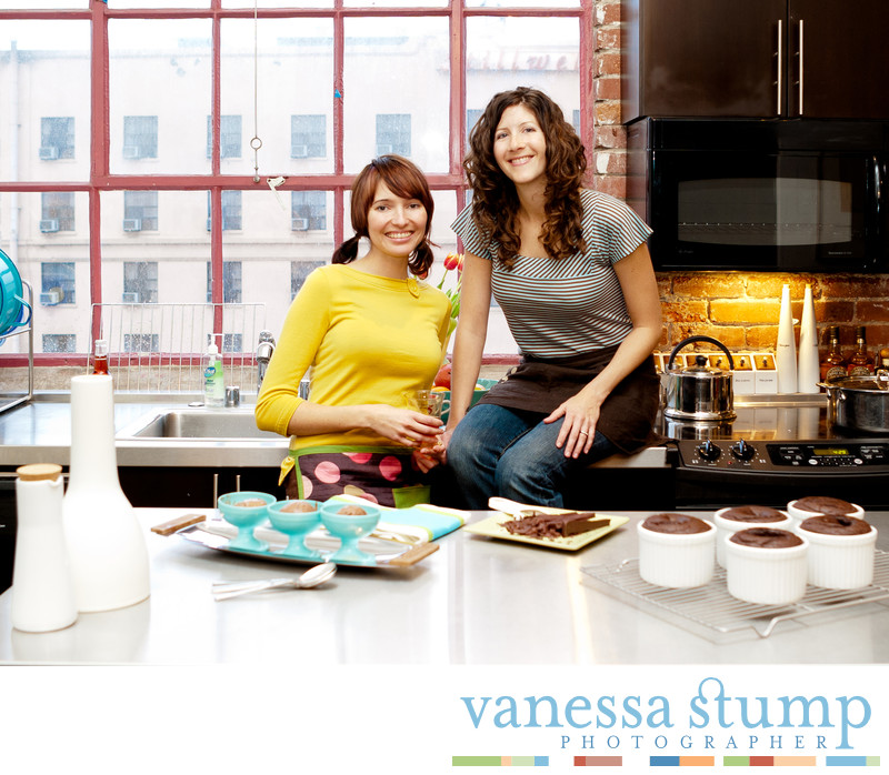 Portrait of two smiling ladies in a kitchen with baked goods.