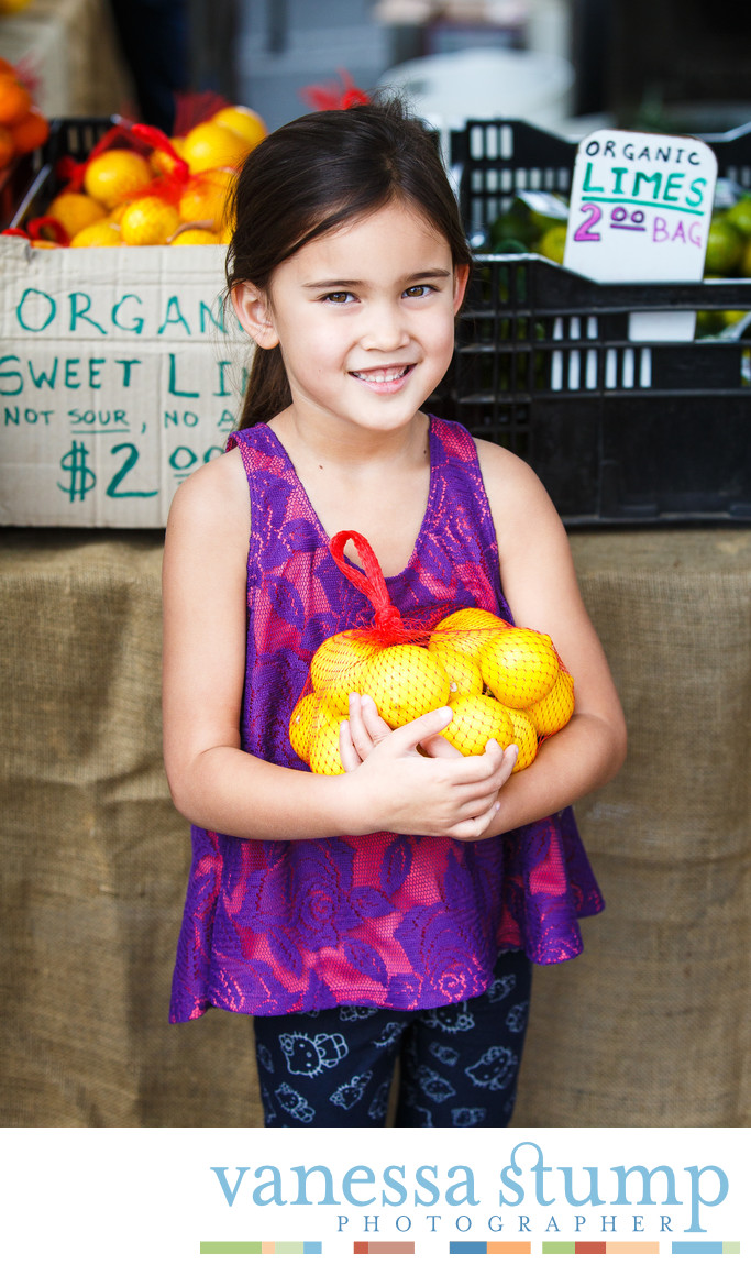 Smiling portrait of young girl at a farmers market holding lemons