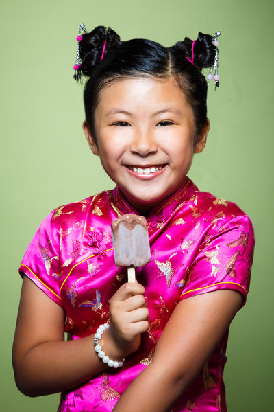 Smiling girl eating popsicle