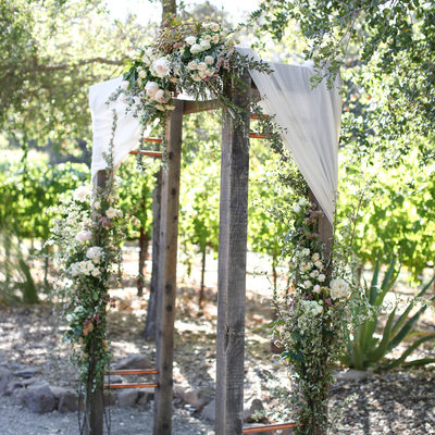 simple wooden wedding arbor with copper elements