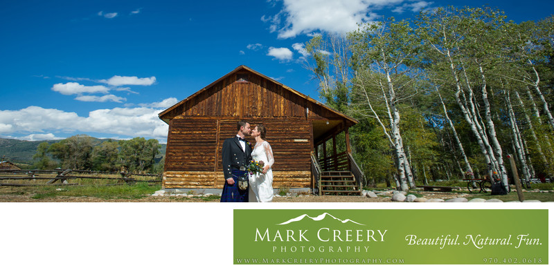 Couple by cabin and aspens in Steamboat Springs wedding