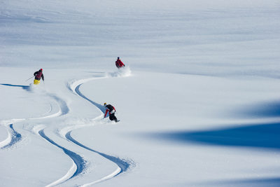 Snowboarders and skier enjoying untracked fresh powder in the Whistler backcountry