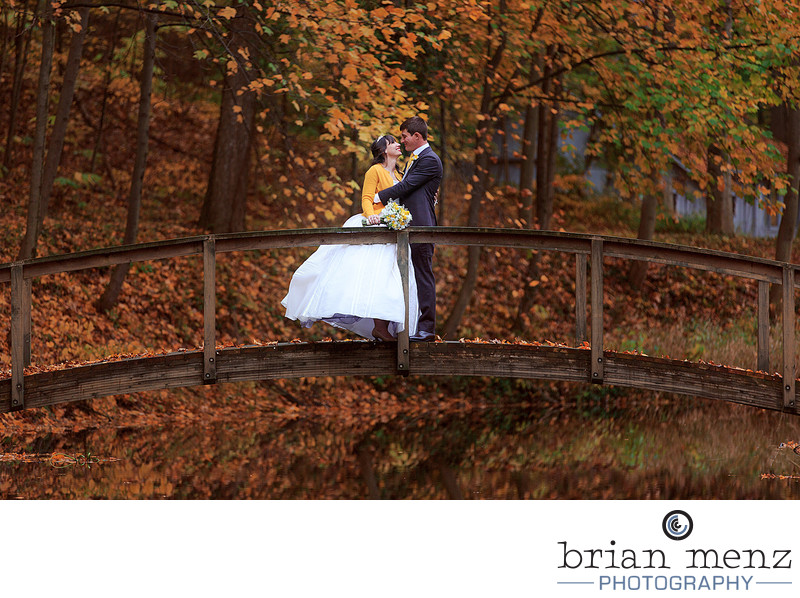 couple-embracing-bridge-fall-leaves