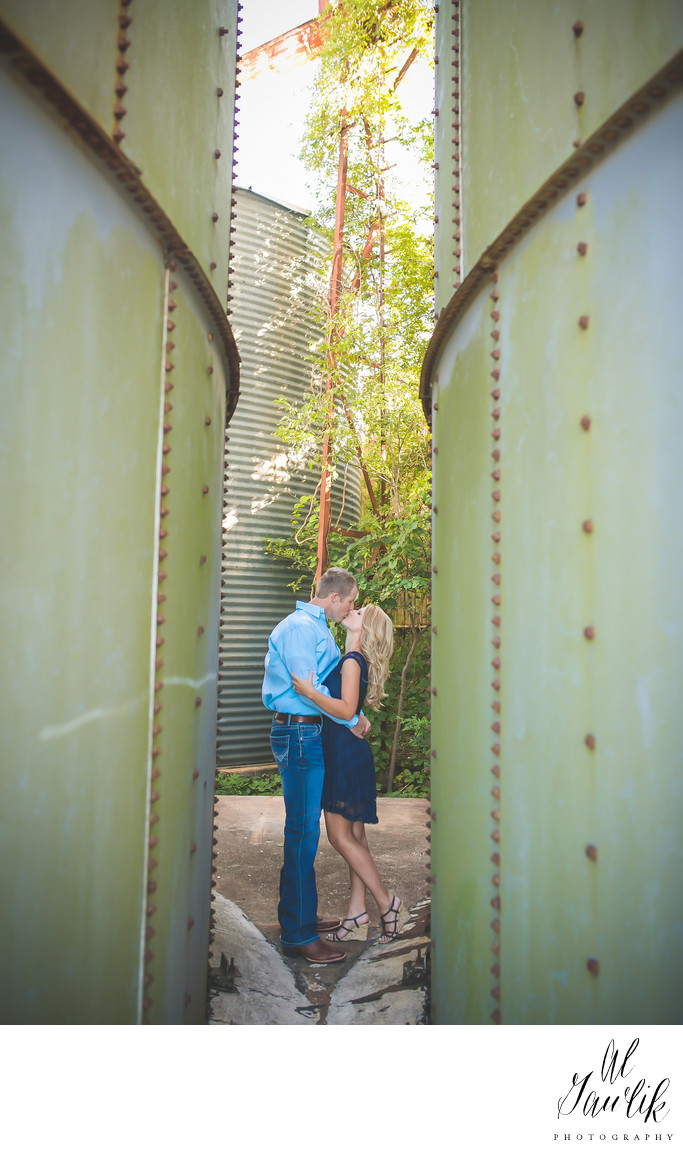 Engagement photo capture between the tall green walls
