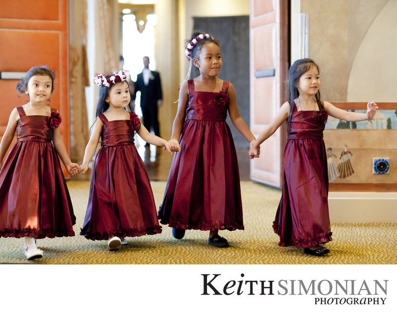 Four flower girls holding hands walking together