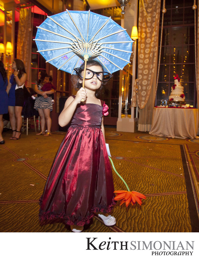 Junior bridesmaid wearing  prop glasses and umbrella
