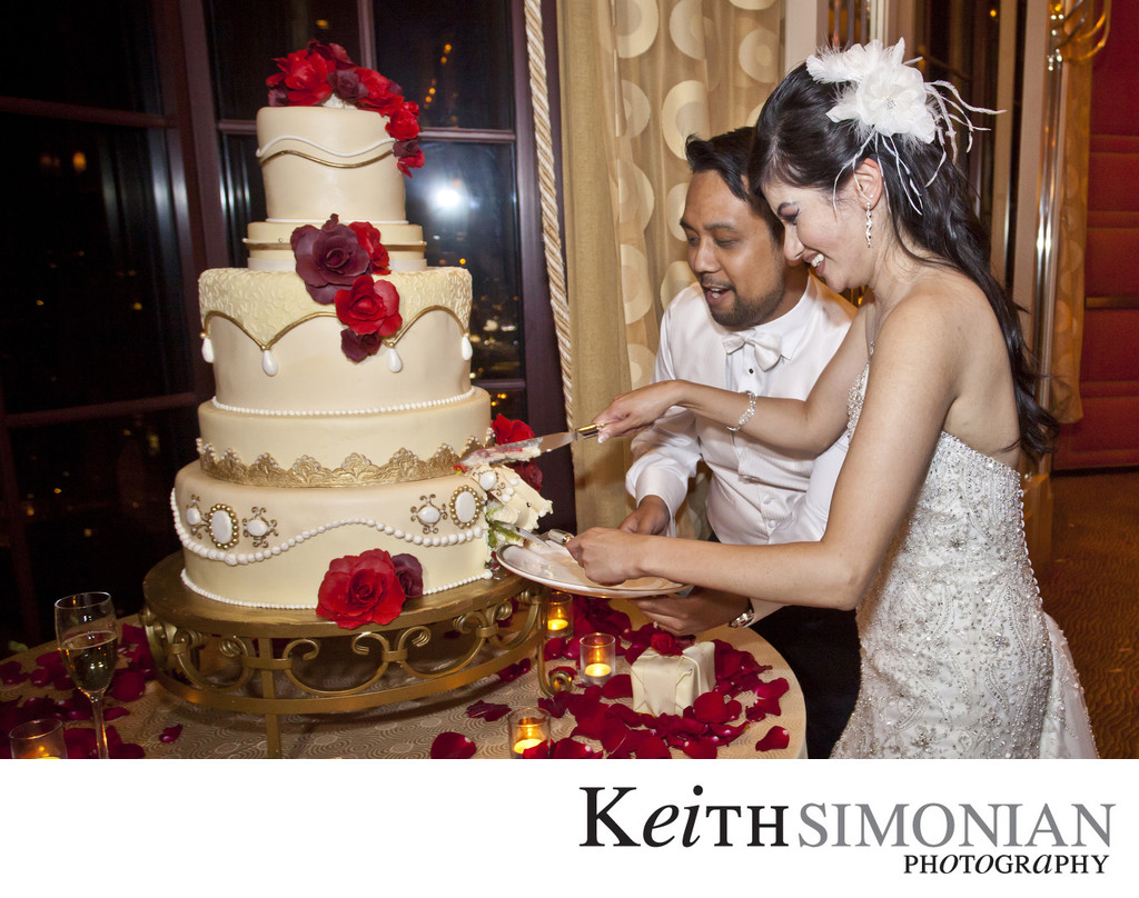 Cutting the five tiered wedding cake