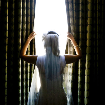 Bride silhouetted in window looking out over Bay Area