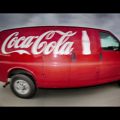 Red Coca Cola van driving down the freeway