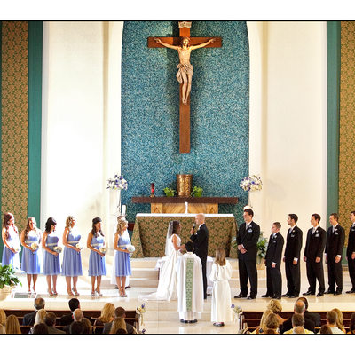 The entire wedding party standing at the alter during mass