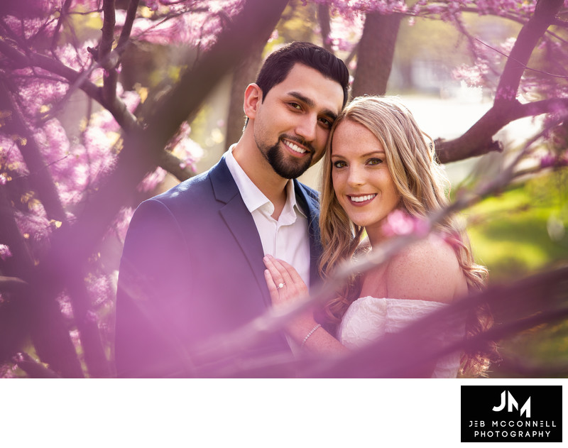 Engaged couple smiling in pink flowers