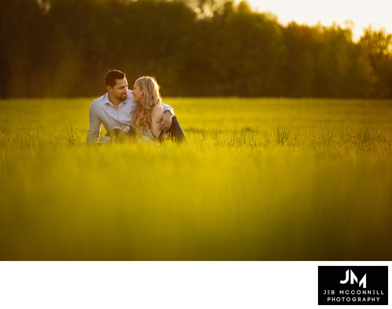 Engaged couple sitting in field at sunset
