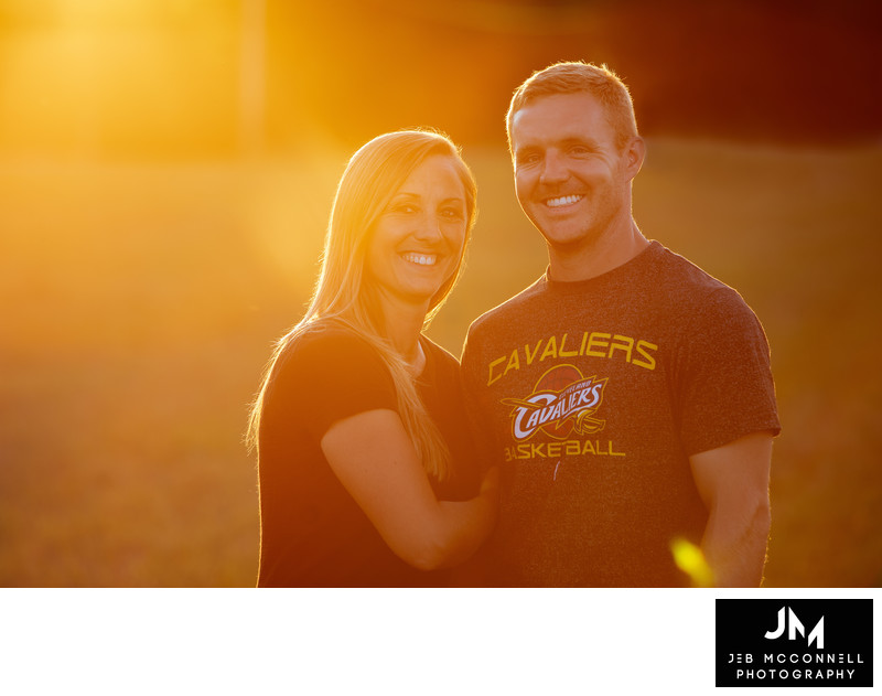Engaged couple posing and smiling at sunset
