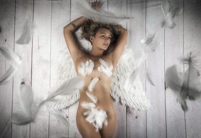 Model laying down covered in feathers