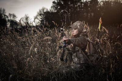 Female bow hunter in field
