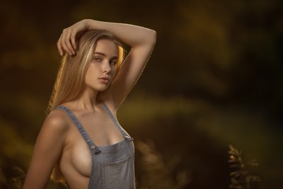 Model topless in overalls