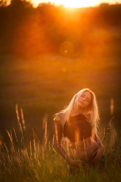 Girl in field at sunset