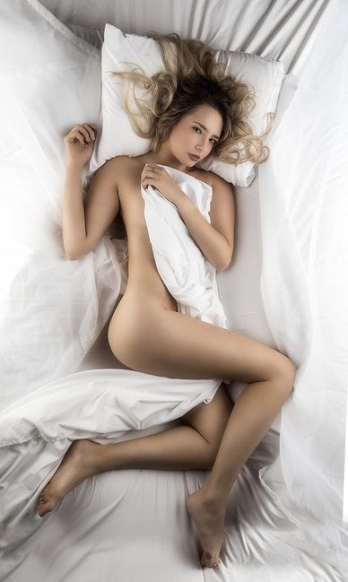 Model laying naked in white sheets