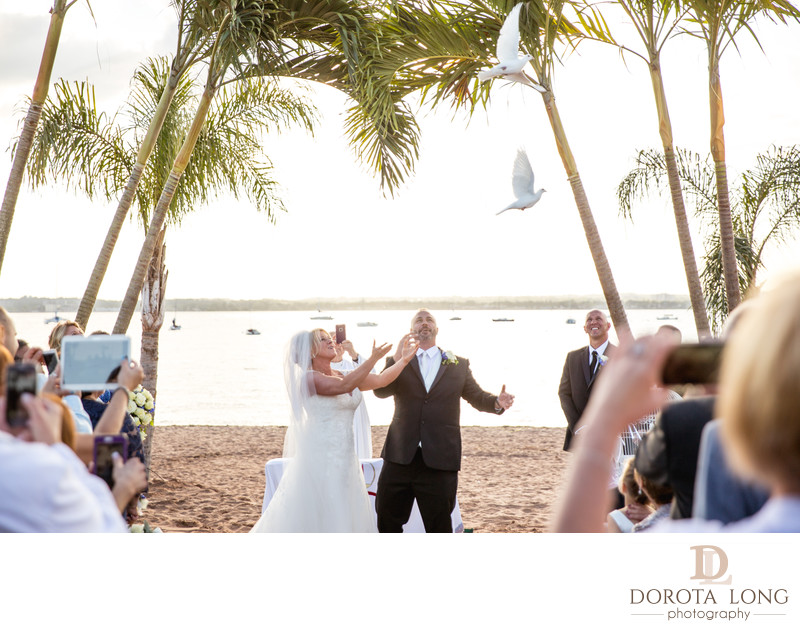 Bride and groom releasing white doves after ceremony