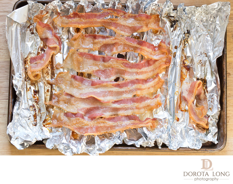baked bacon strips on foil on cooking sheet